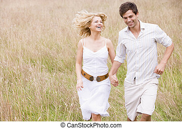 Couple running outdoors holding hands smiling