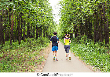 Couple running outdoors. Woman and man runners jogging together outside in full body length.