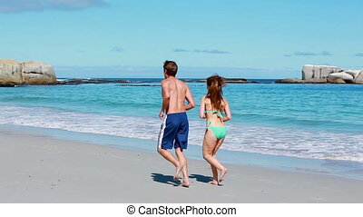 Couple running side by side on the beach