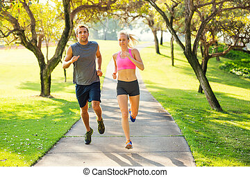 Couple running together in the park - Athletic couple...
