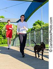 Couple running with dog across the bridge
