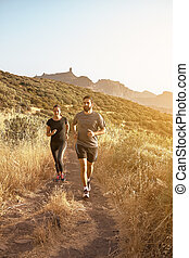 Couple running with mountains in the background - Running...