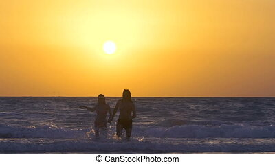 Couple runs and enjoys on the beach at sunset. Happy Man with woman is holding hands and running on the shore of the sea in water. Two people in love, have fun under the sun. Slow motion