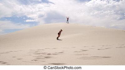 Couple sand boarding in the desert 4k