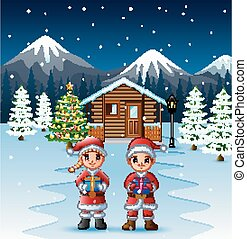 Couple santa claus holding a box gift in front of the snowy wooden house