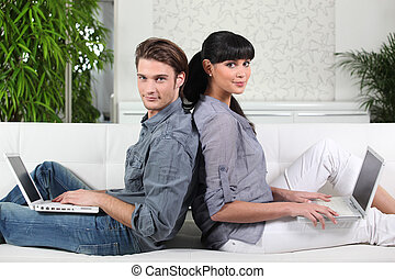 Couple sat back to back each with a laptop
