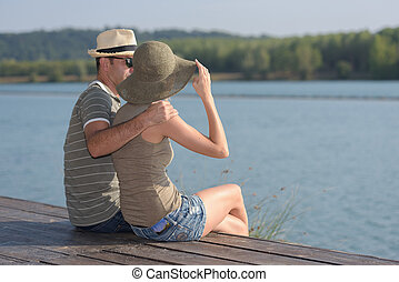Couple sat embracing on pier