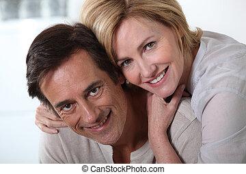 Couple sat hugging looking at camera