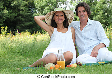 Couple sat in field