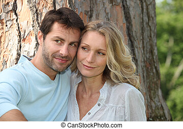 Couple sat in front of tree