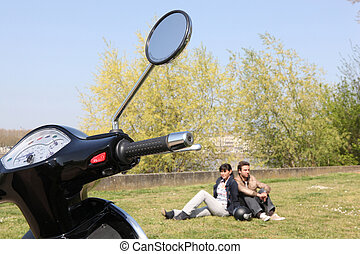 Couple sat near scooter