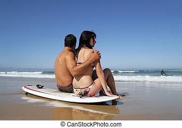 Couple sat on a surfboard