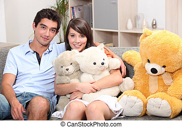 Couple sat on couch with cuddly toys