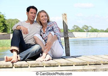 Couple sat on jetty