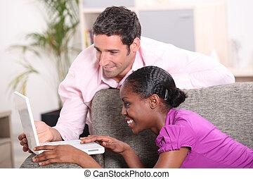Couple sat on sofa using laptop