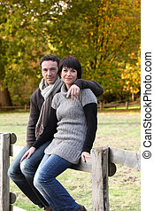 Couple sat on wooden fence