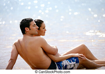 Couple sat together on a  beach