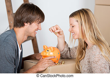 couple saving money - couple moving and thowing coins in a ...