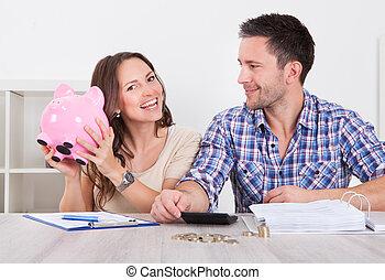 Couple Saving Money - Young Man Looking At Woman Inserting...