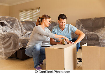 couple sealing moving boxes in their old home