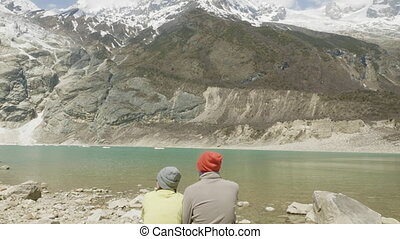 Couple seat at the mountain lake Birendra in Nepal. Manaslu area.