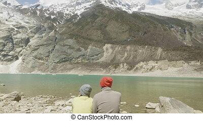 Couple seat at the mountain lake Birendra in Nepal. Manaslu area.
