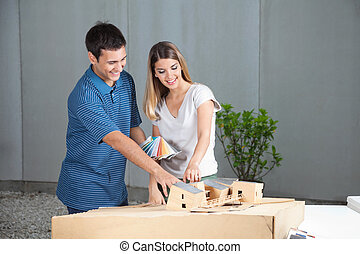 Couple Selecting Colors For Model House - Happy young couple...