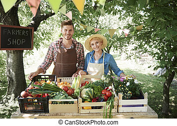 Couple selling vegetables in farmers market
