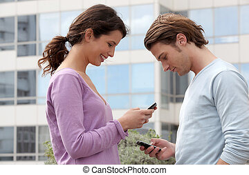 Couple sending text messages outside