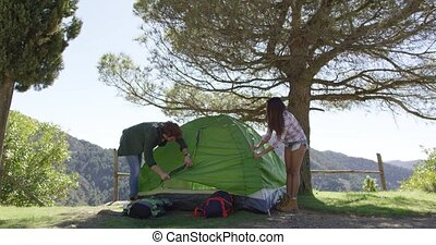 Couple setting tent under trees - Young people putting up...