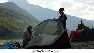 Couple setting up tent near riverside 4k - Couple setting up...
