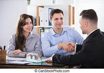 Couple Shaking Hands With Real Estate Advisor