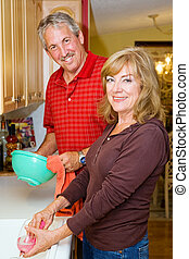 Couple Shares Chores - Beautiful mature couple sharing the...