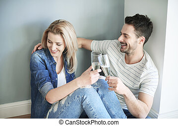 Couple sharing champagne whilst moving