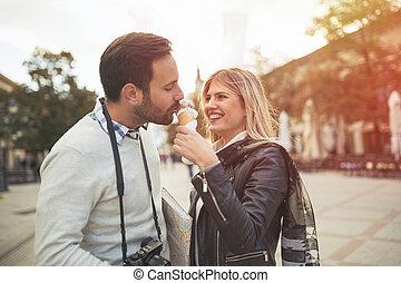 Couple sharing ice cream outdoors