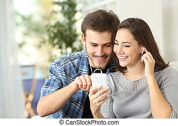 Couple sharing music from smart phone