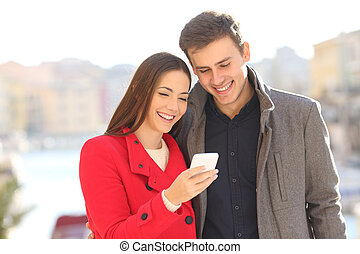 Couple sharing smart phone in winter