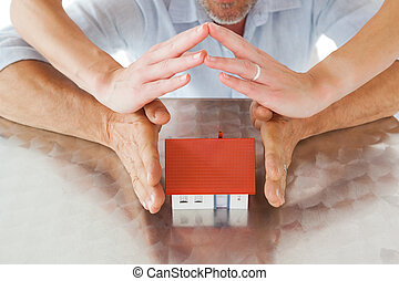 Couple sheltering miniature house with hands on white ...