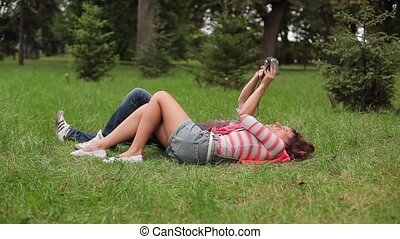 Couple shoot themselves at the camera on the grass