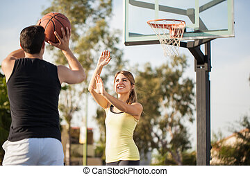 Couple shooting hoops outdoors - Hispanic young woman trying...