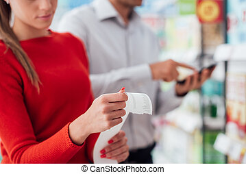 Couple shopping and checking a receipt
