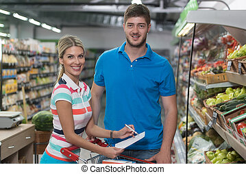 Couple Shopping At The Supermarket With Grocery List