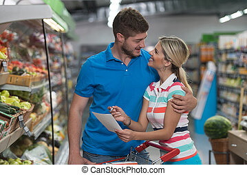 Couple Shopping At The Supermarket With Grocery List -...