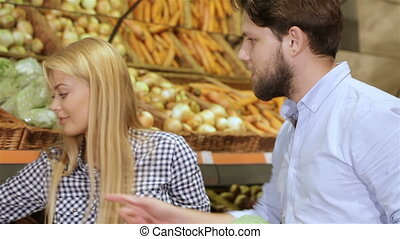 Couple shopping at the vegetable section of supermarket