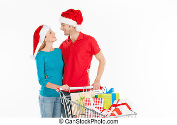 Couple shopping. Cheerful young couple standing near shopping cart and looking at each other while isolated on white