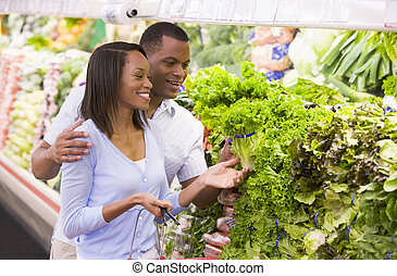 Couple shopping in produce department - Couple shopping in...