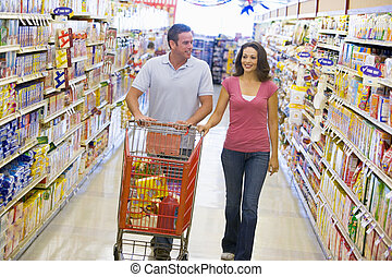 Couple shopping in supermarket aisle - Couple shopping in...