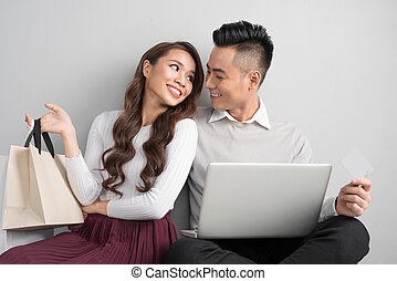 Couple shopping online. Happy couple looking together sitting floor at home