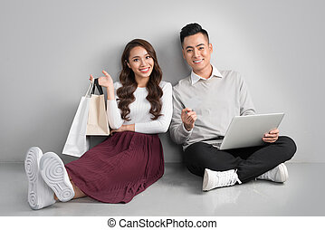 Couple shopping online. Happy couple sitting floor at home