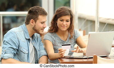Couple shopping online in a coffee shop